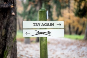 Signboard with two signs saying - Try again - Give up - pointing