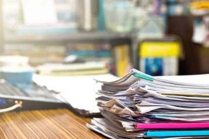 Pile of unfinished homework assignment documents on the teacher's desk